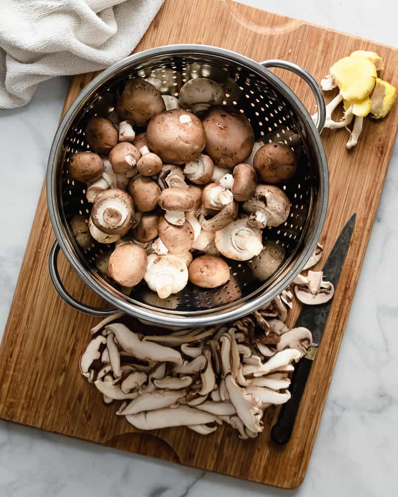 a variety of mushrooms on cutting board and in colander