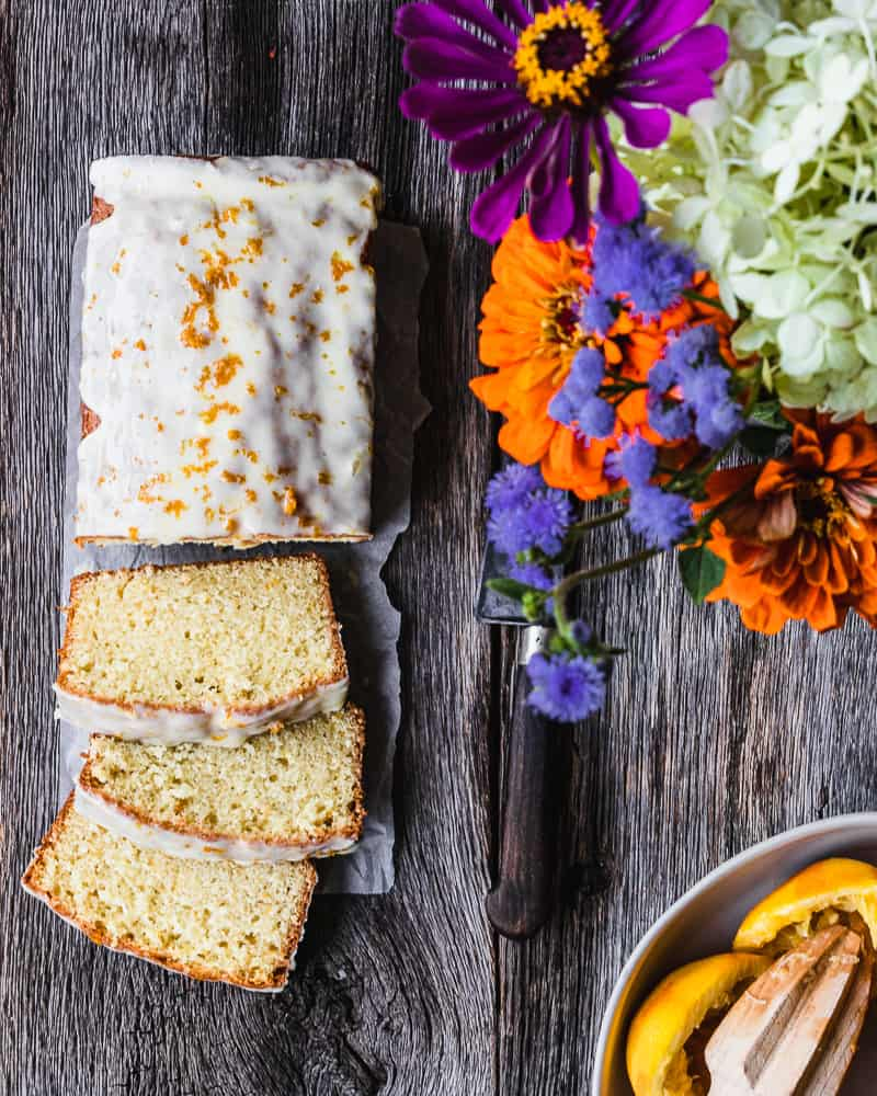 orange pound cake with flowers and juiced oranges in frame