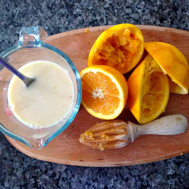 liquid ingredients in measuring cup and sliced, juiced oranges