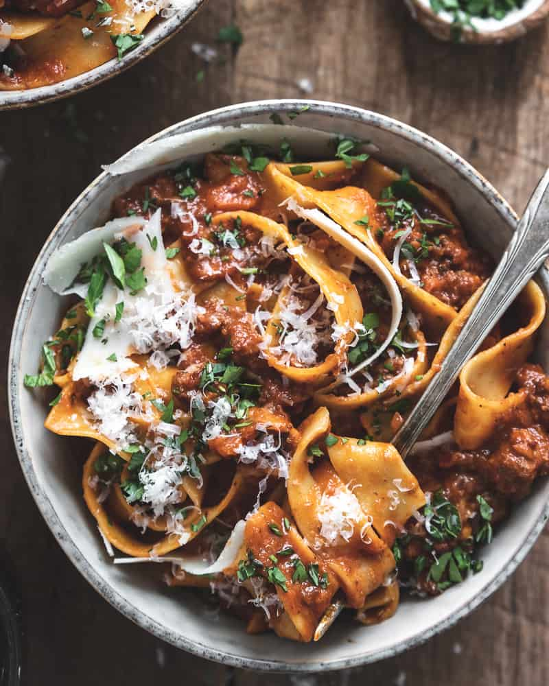 bowl of pappardelle pasta with authentic bolognese sauce, cheese, and herbs