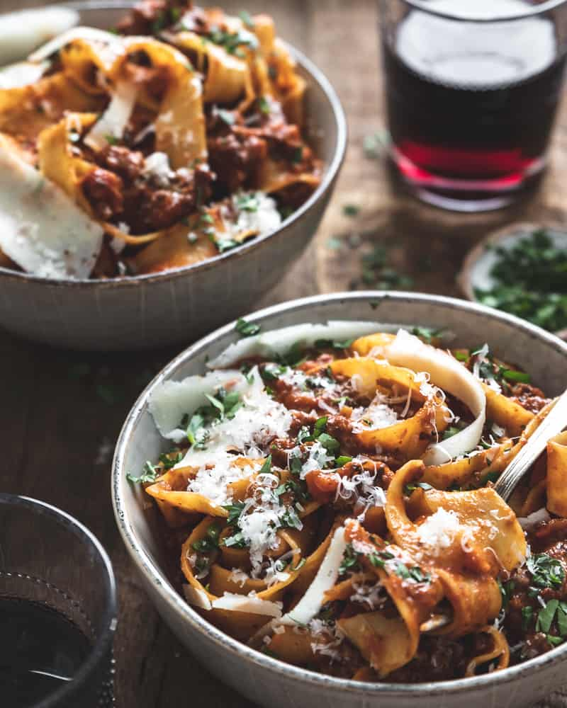 front 45 degree angle of two bowls of pappardelle bolognese with cheese and herbs and two glasses of red wine