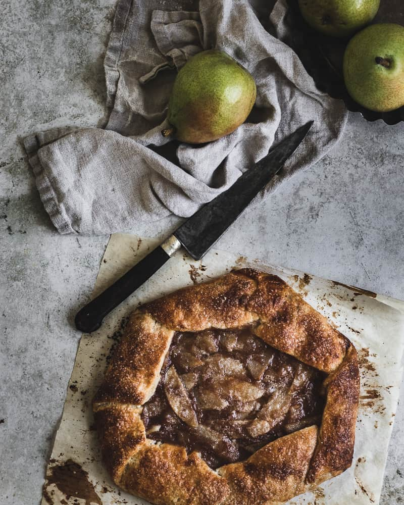 pear galette after baking on parchment with knife, kitchen towel, and fresh pears