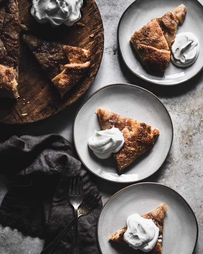 sliced pear galette on cutting board next to three plates with galette slices topped with whipped cream