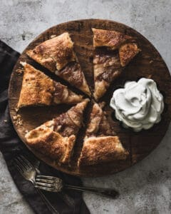 sliced pear galette on wooden cutting board with dish of whipped cream