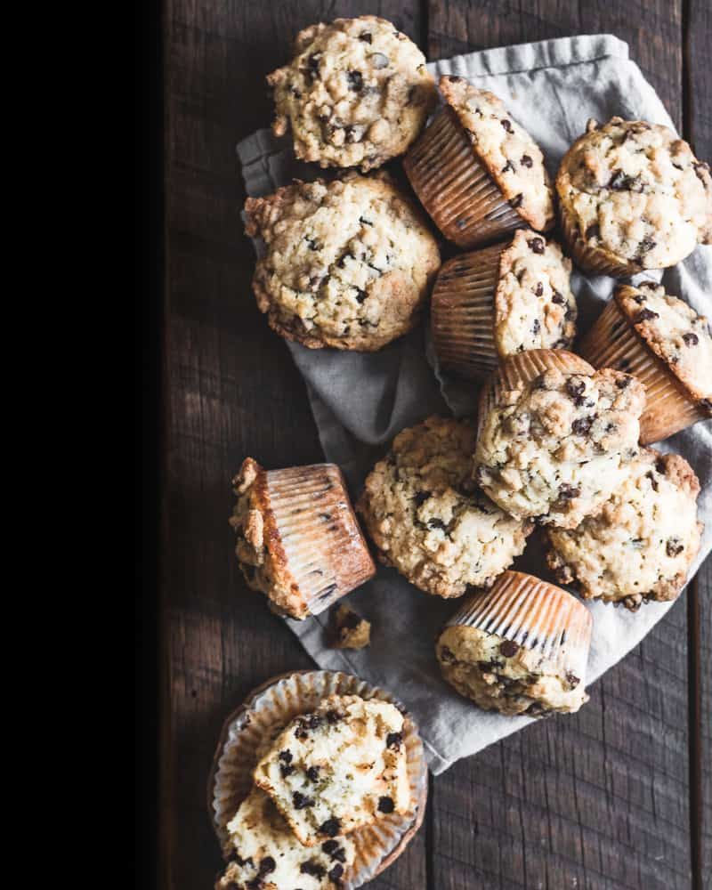 overhead view of 12 chocolate chip muffins on a tan linen napkin and wooden table