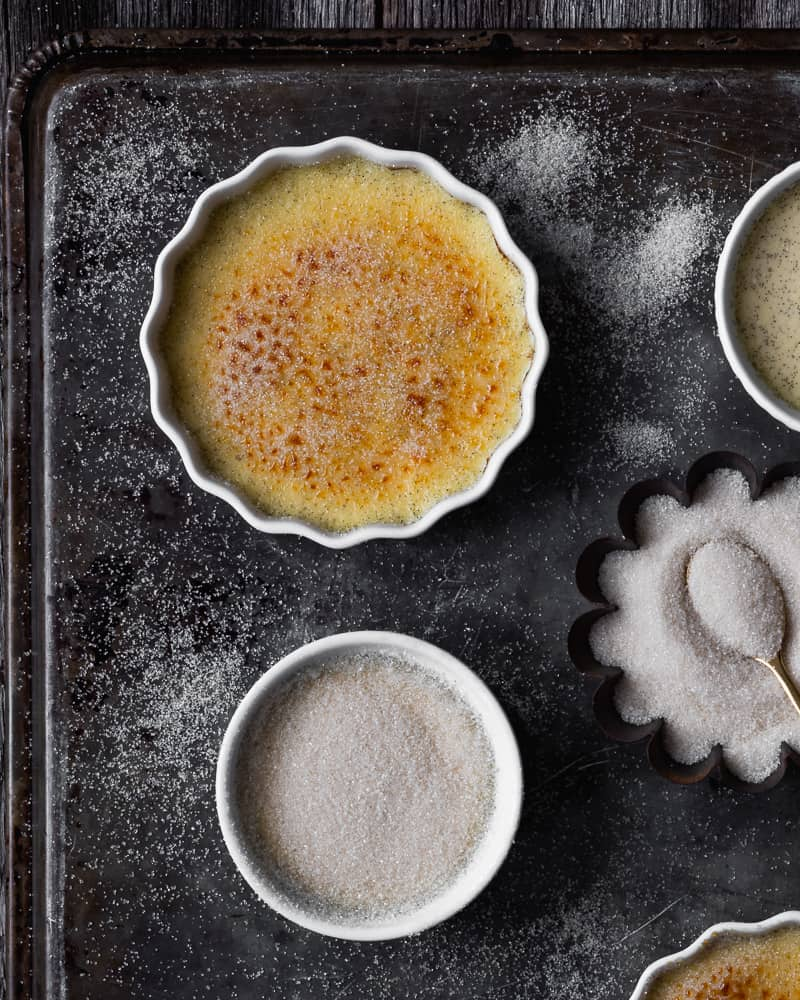 creme brulee in ramekins on baking tray with sugar