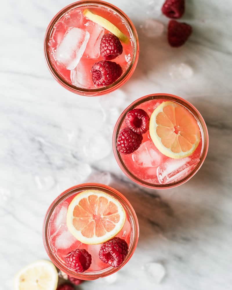 three jars of raspberry lemonade on marble surface