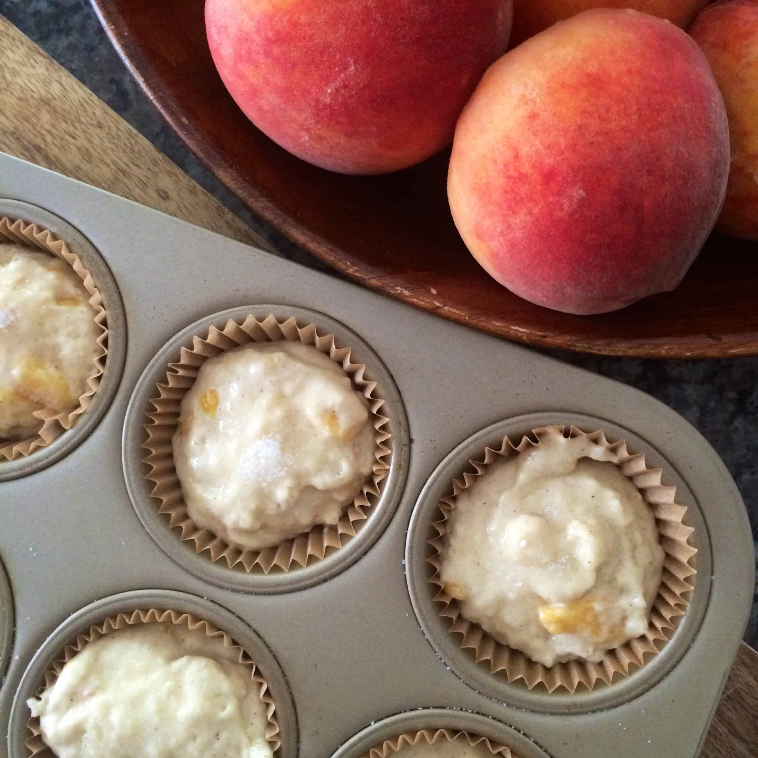 muffin batter before baking and a bowl of fresh peaches