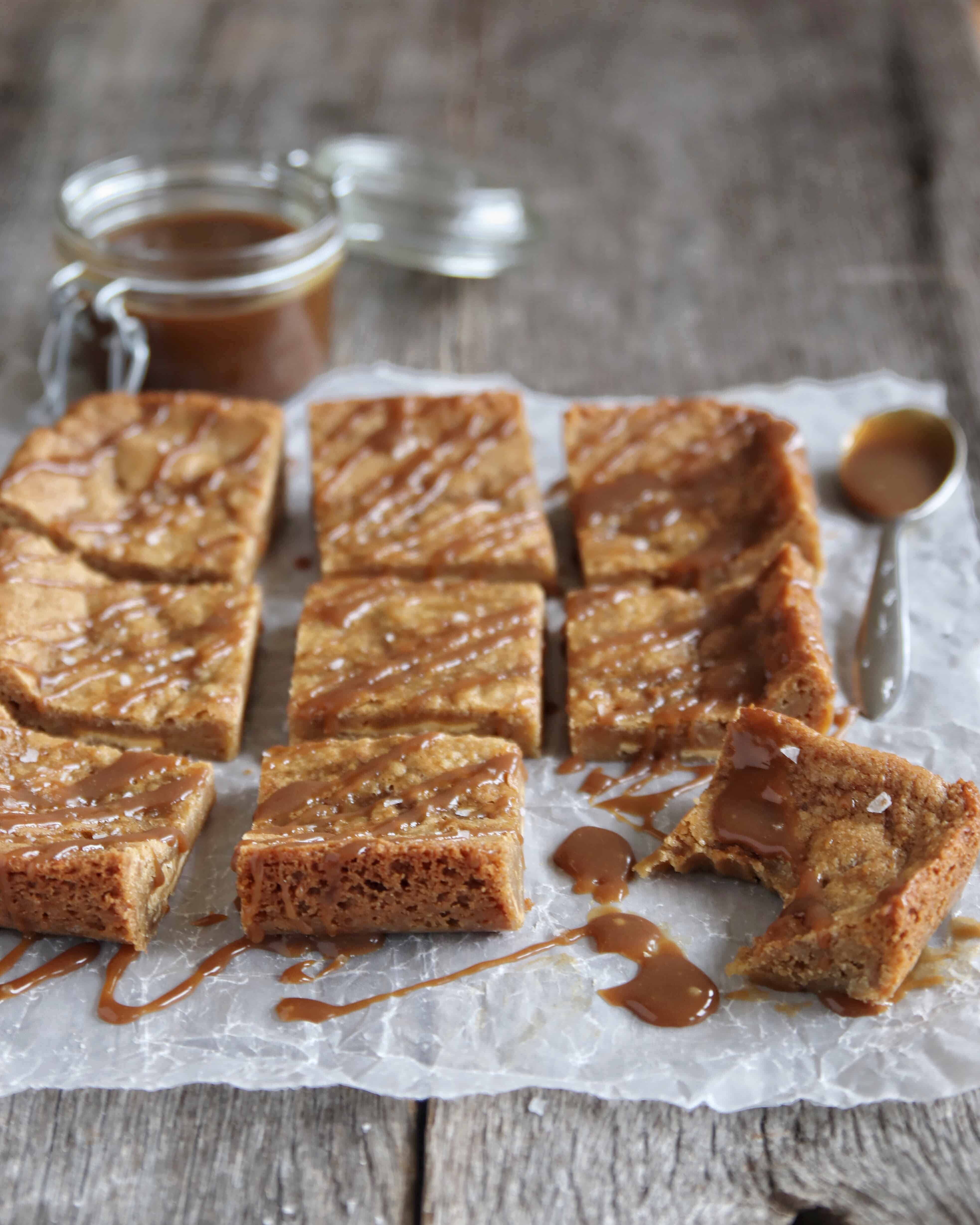 blondies on parchment drizzled with butterscotch sauce