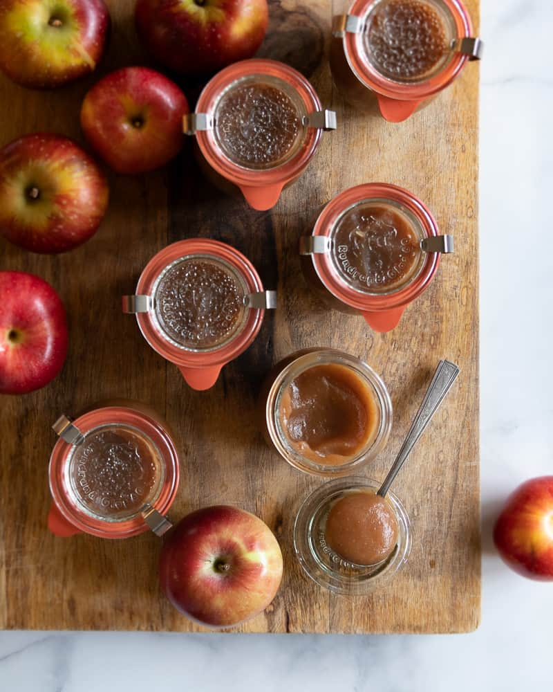 apples and jars of apple butter on cutting board