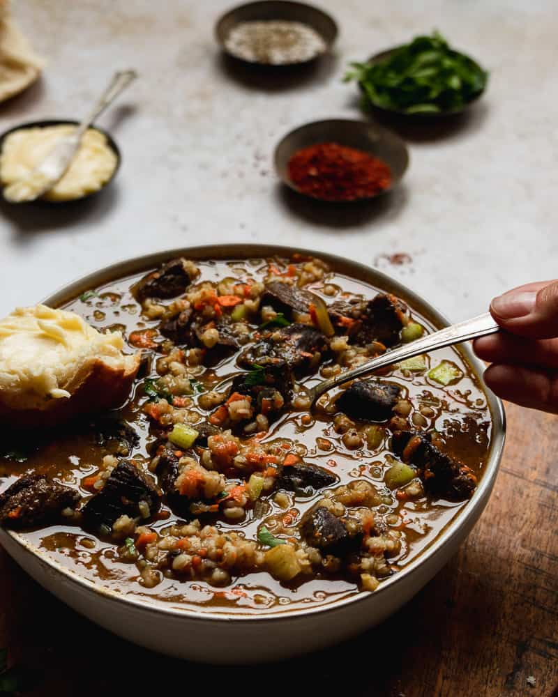 Front shot of beef and barley soup with hand in frame holding spoon