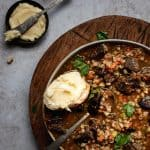 bowl of beef and barley soup with buttered bread