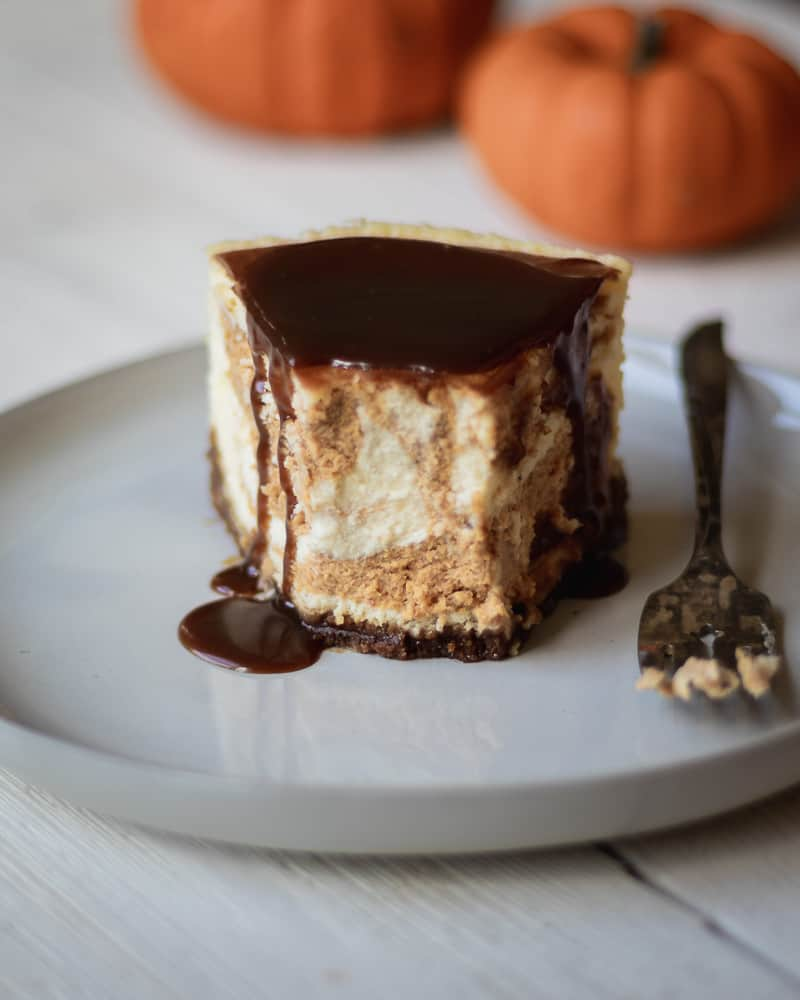 one slice of pumpkin swirl cheesecake on plate with fork