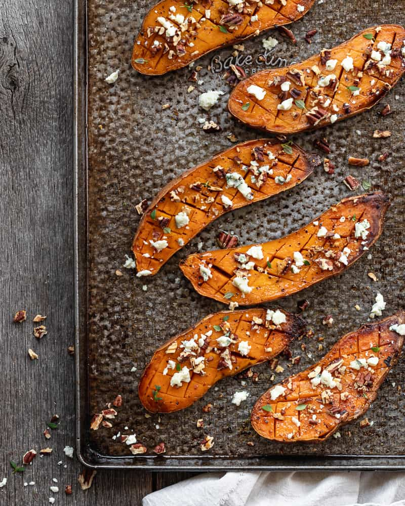 Roasted sweet potatoes on baking tray topped with crumbled blue cheese and chopped pecans