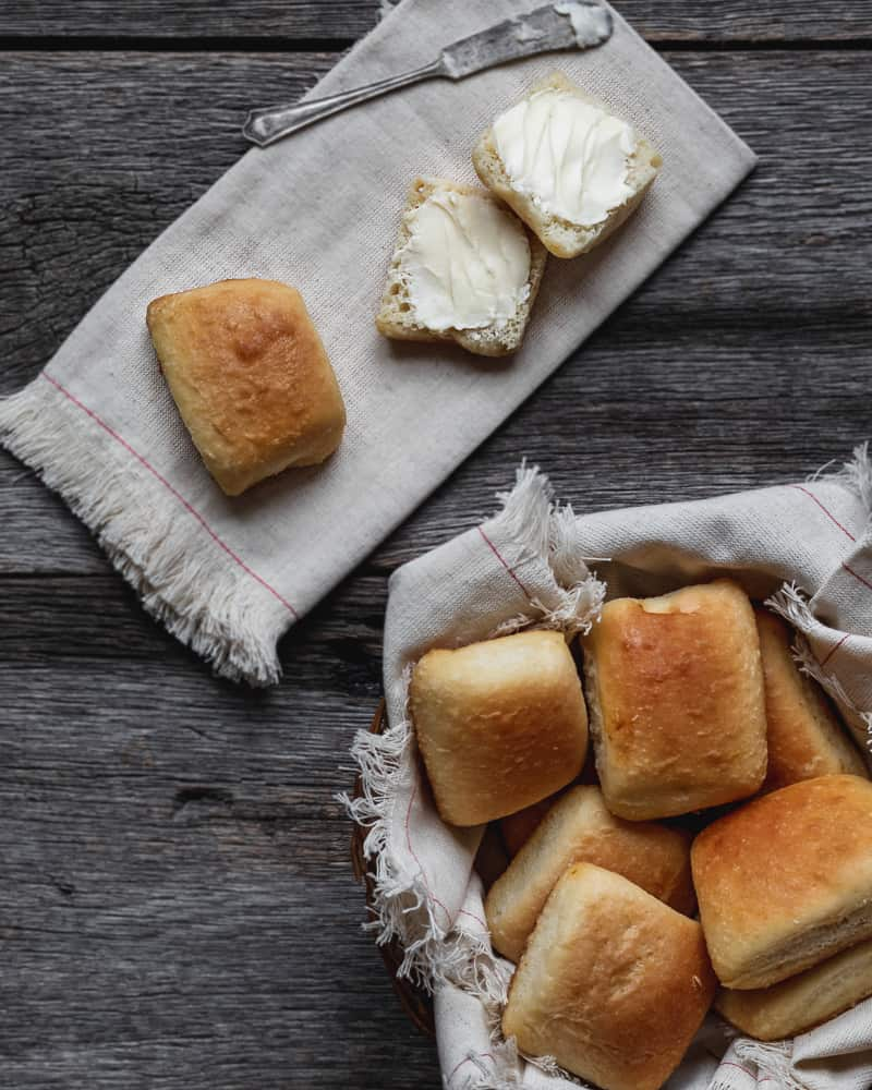 yeast rolls in basket, one sliced and buttered