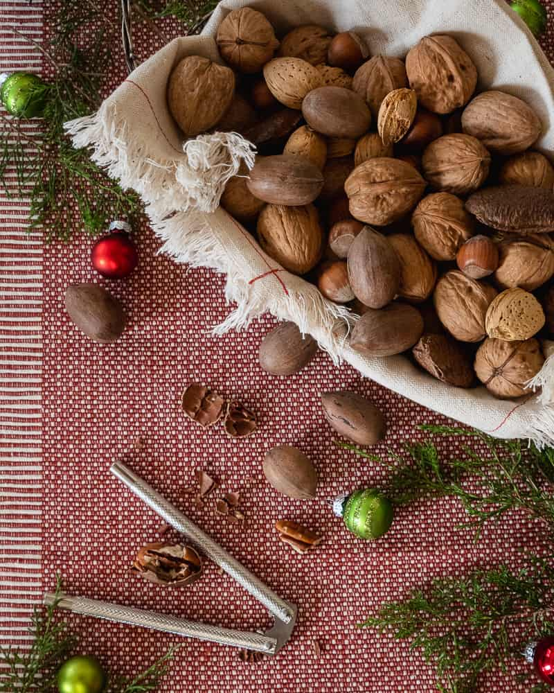 bowl of in-shell nuts with holiday greenery and decorations