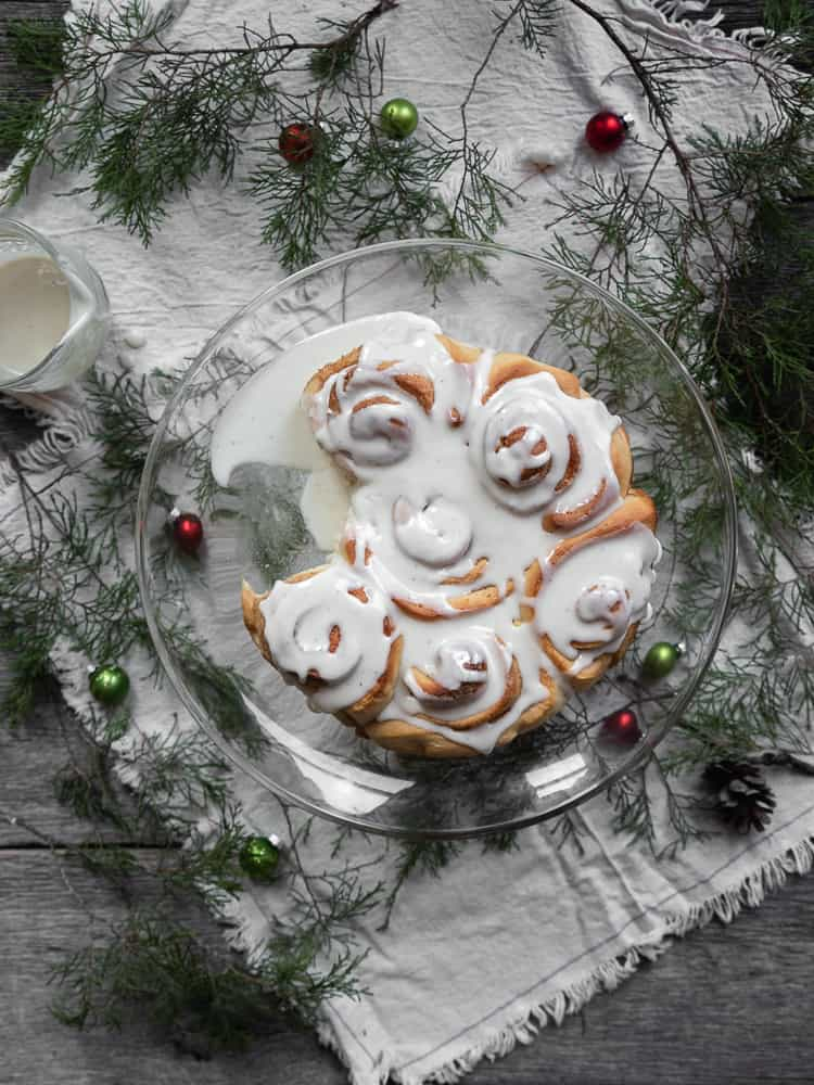 eggnog sweet rolls on cake stand surrounded by holiday greenery and decor