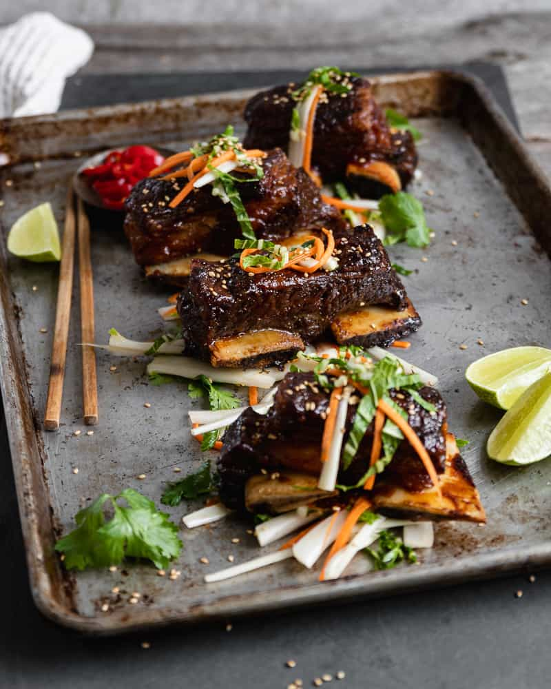 Asian style beef short ribs on baking tray with garnishes