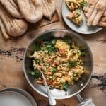 Afghan scrambled eggs in pan surrounded by plates and afghan naan
