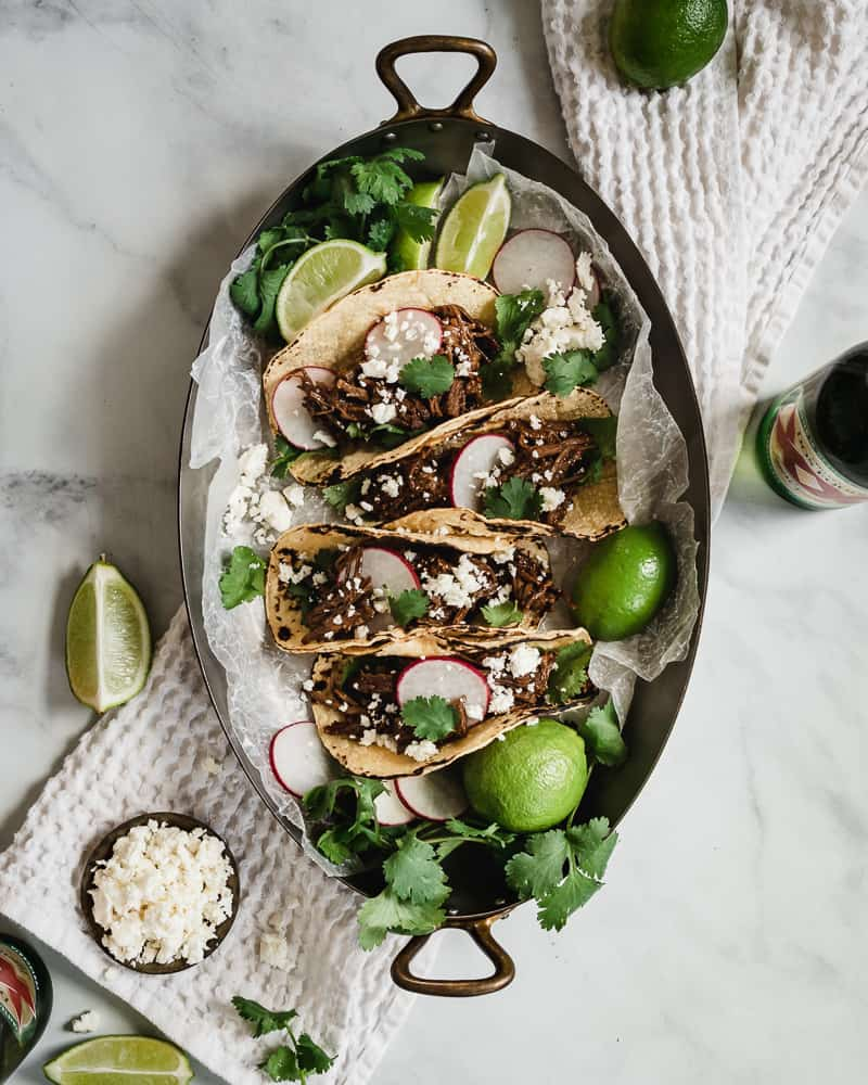 barbacoa beef tacos in serving tray with toppings and beer