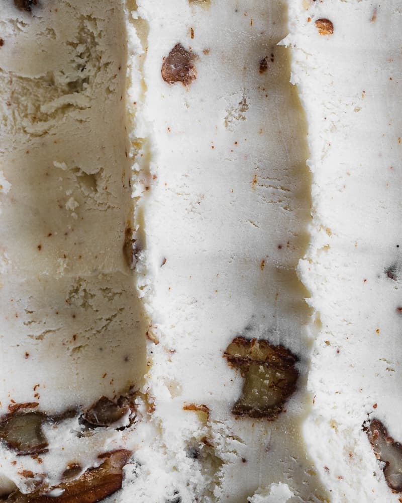 butter pecan ice cream in dish with long scoops taken out
