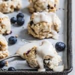 glazed scones on baking tray with blueberries