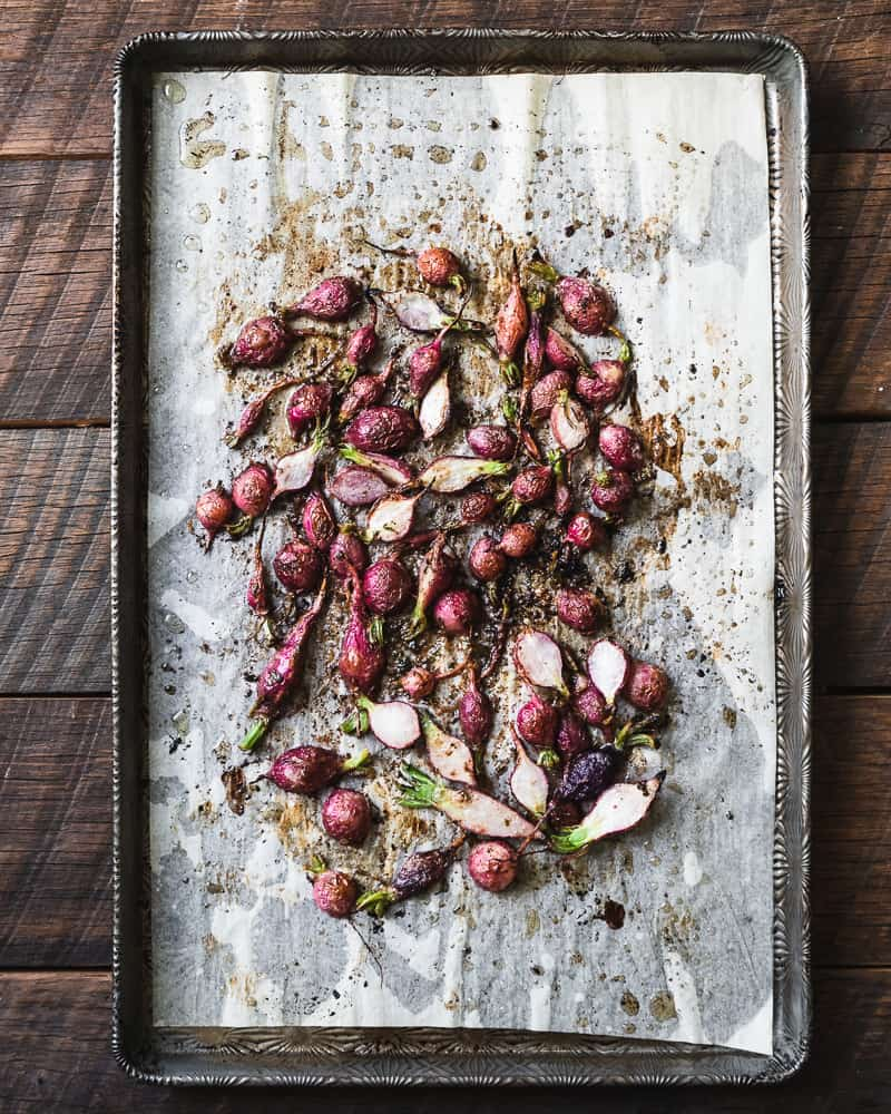 roasted radishes on parchment lined sheet tray