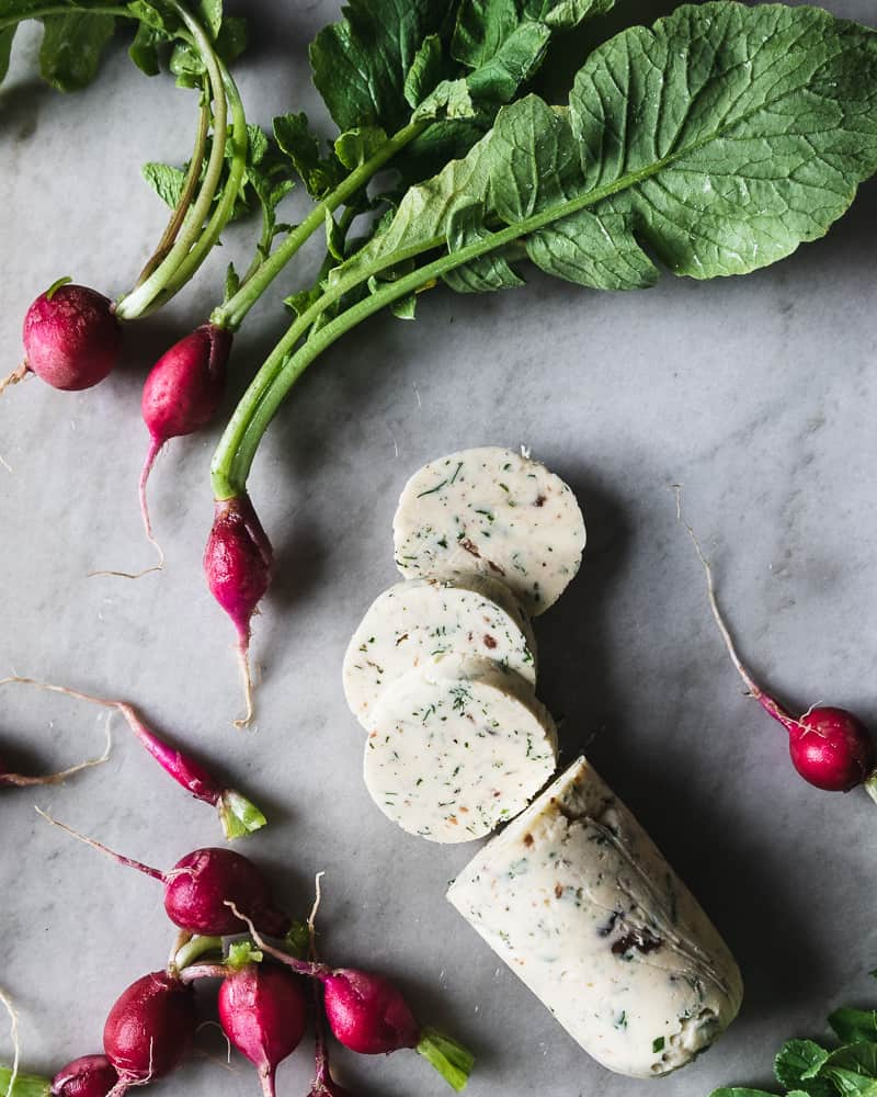 fresh radishes and compound butter on marble surface