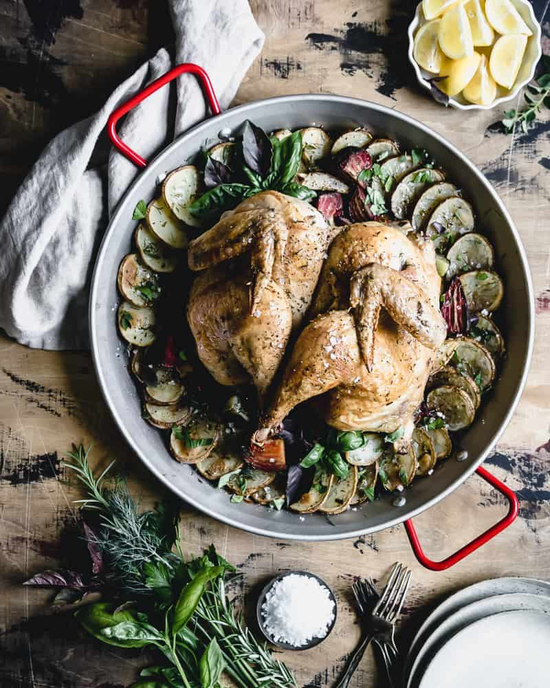 overhead shot of roast chicken with vegetables in large round baking dish
