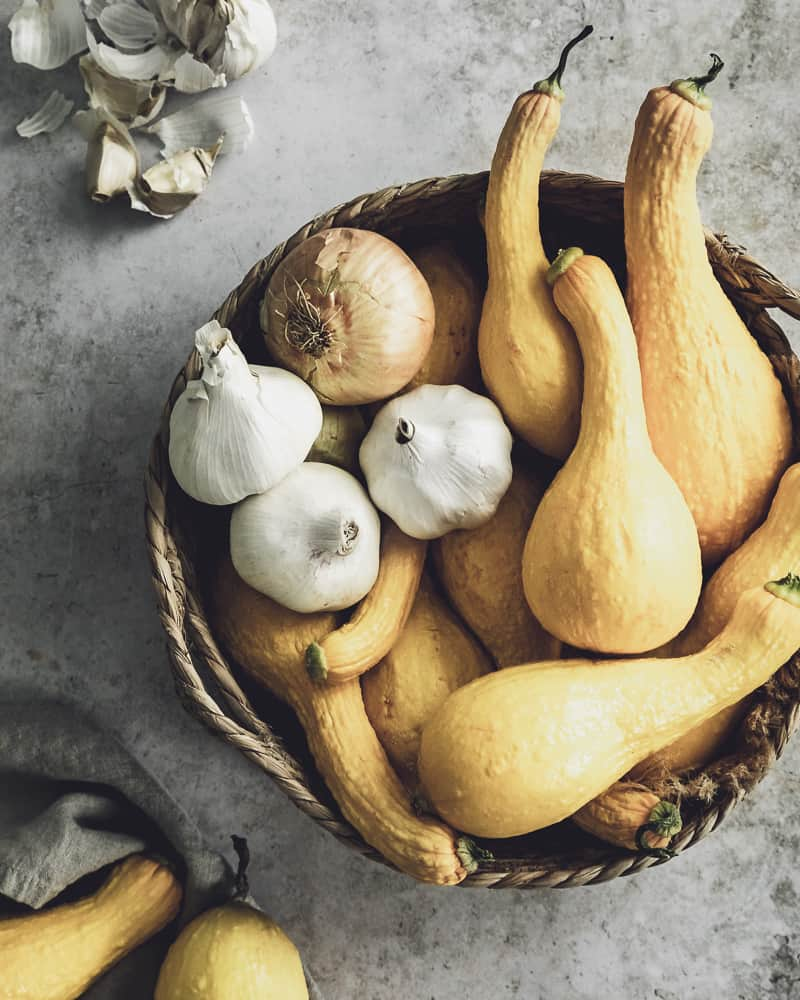 Basket of fresh yellow squash, onions and garlic