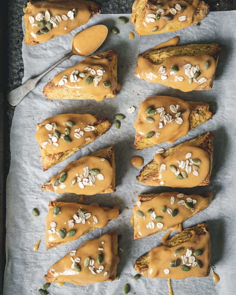 overhead view of baked and glazed pumpkin scones on parchment lined baking sheet with spoon of glaze and oats and pepitas