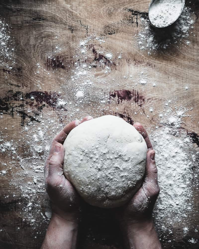 overhead view of hands cradling a ball of basic pizza dough