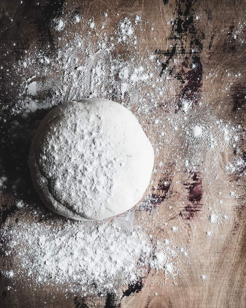 pizza dough ball on floured surface