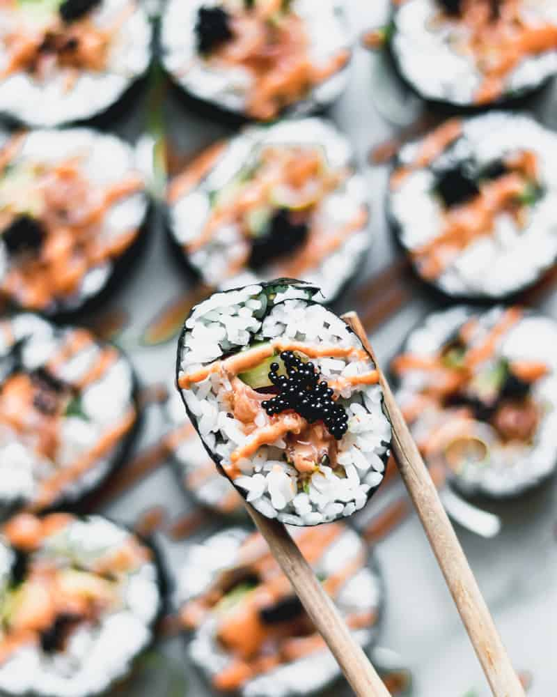 overhead view of spicy salmon roll being held with chopsticks