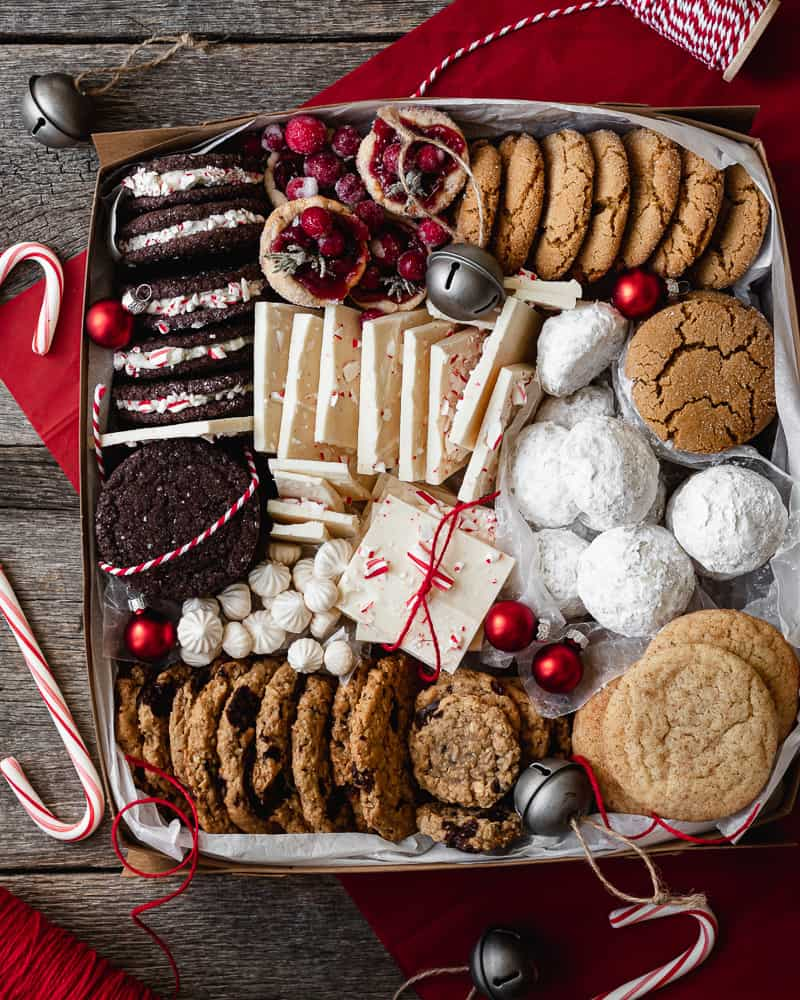 overhead view of Christmas Cookie Box with a variety of cookies, treats, candy canes, and holiday ornaments and twine