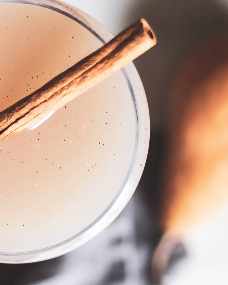 overhead close up shot of cocktail with vanilla bean flecks and cinnamon stick
