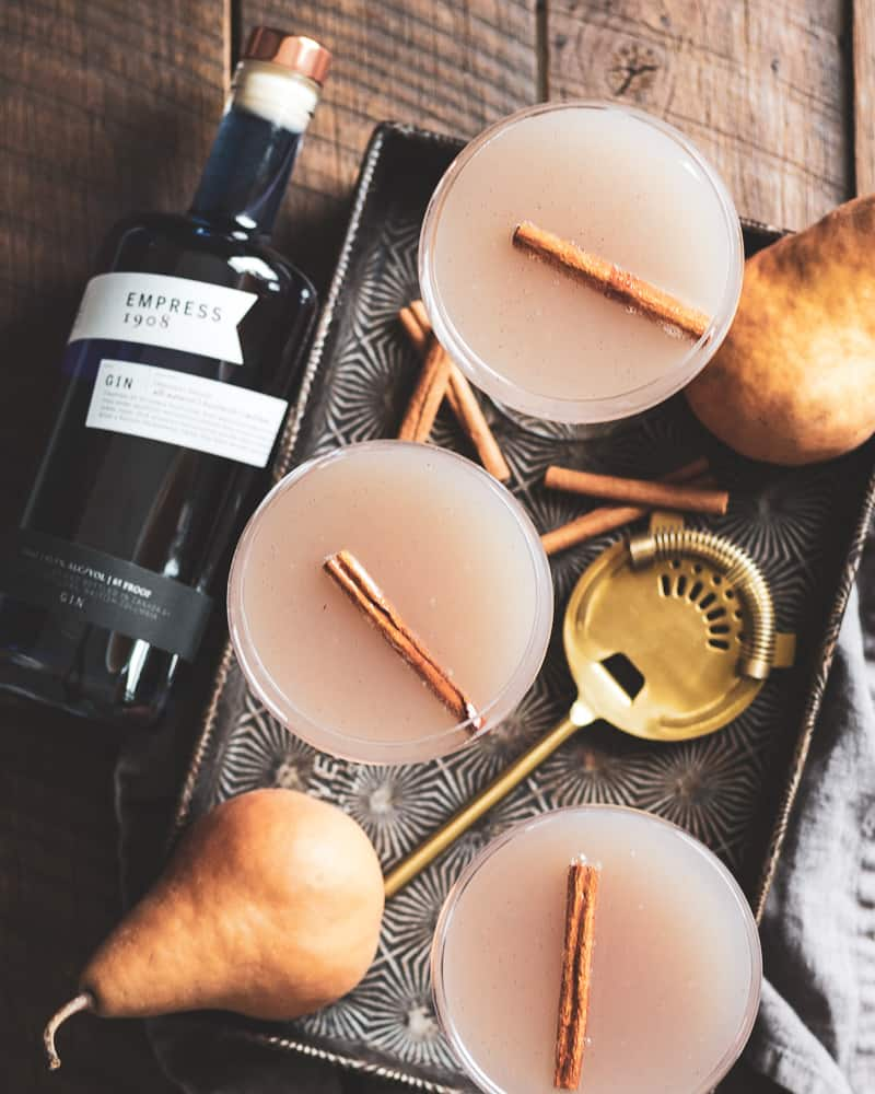 Overhead shot of 3 spiced pear and vanilla bean gin fizz cocktails in vintage baking tray with cinnamon sticks, cocktail shaker, and bottle of empress gin