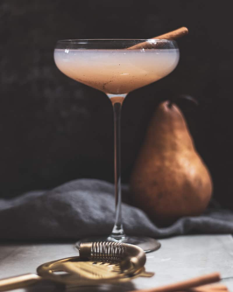 Front shot of pear and vanilla bean gin fizz in a coupe glass with pear in background and cocktail strainer in foreground