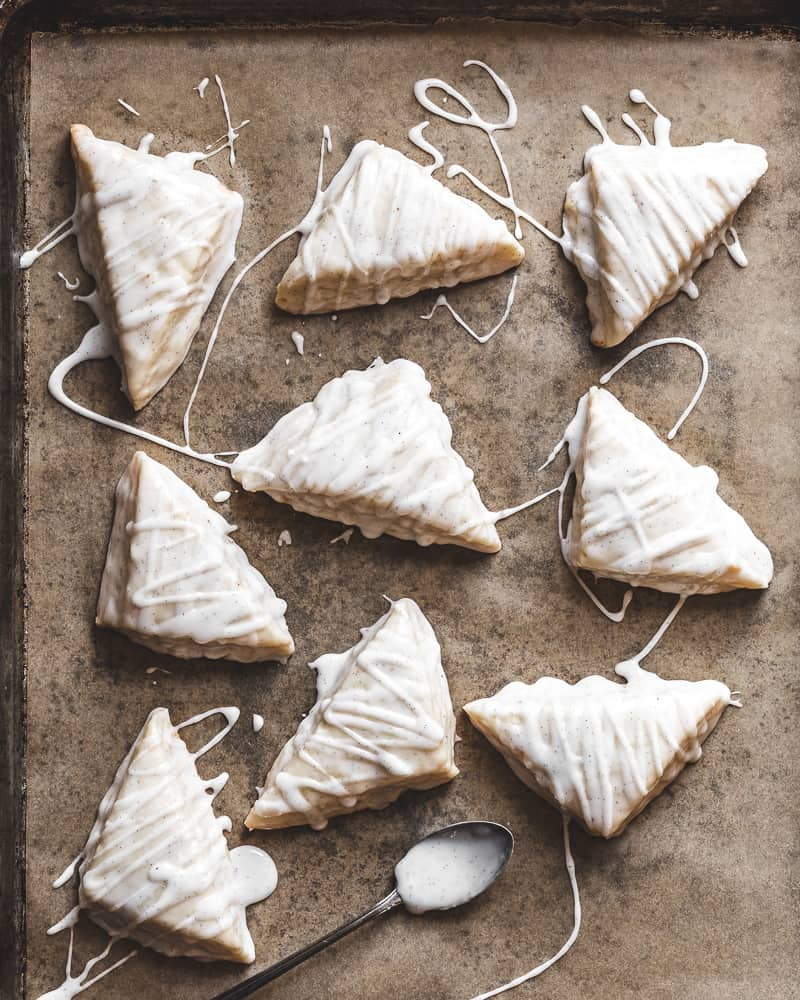 Overhead view of glazed vanilla bean scones on parchment lined baking tray