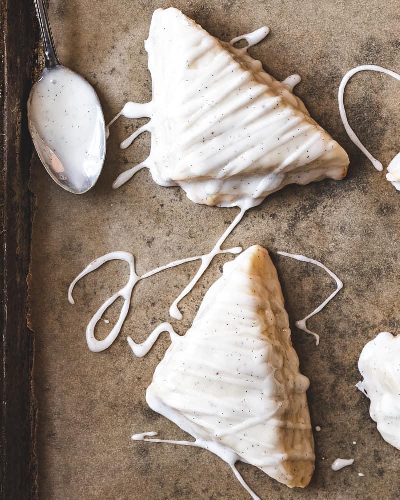 glazed vanilla bean scones on baking tray with spoon of glaze
