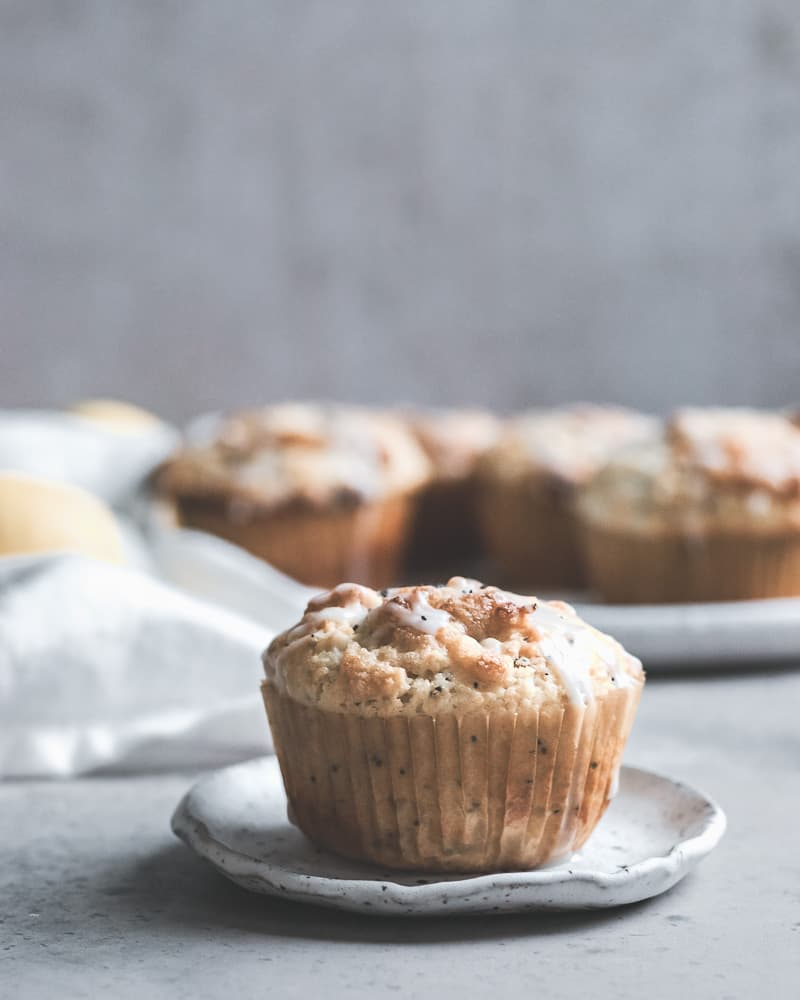 image of one lemon poppy seed muffin on a small white plate with a large plate of muffins in the background
