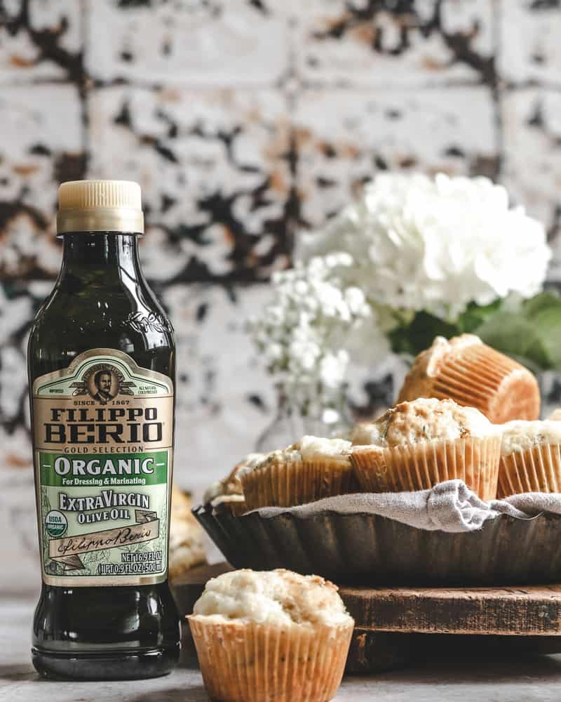 savory muffins in vintage tray with linen next to bottle of olive oil and white flowers