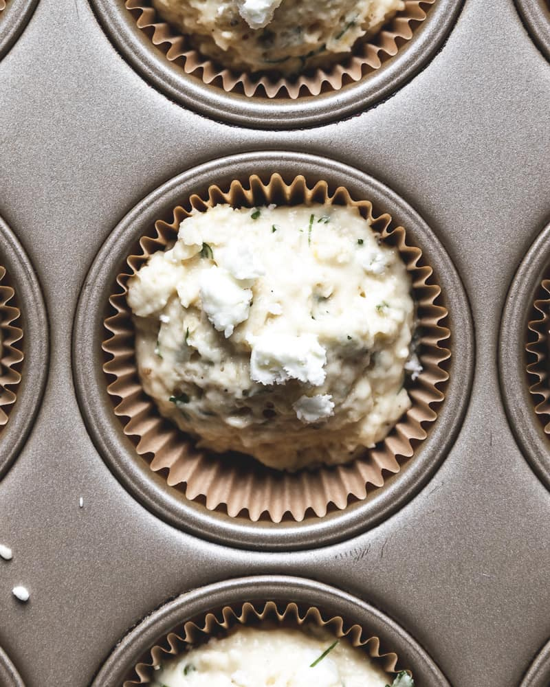 close up of unbaked savory muffin with feta crumbles on top