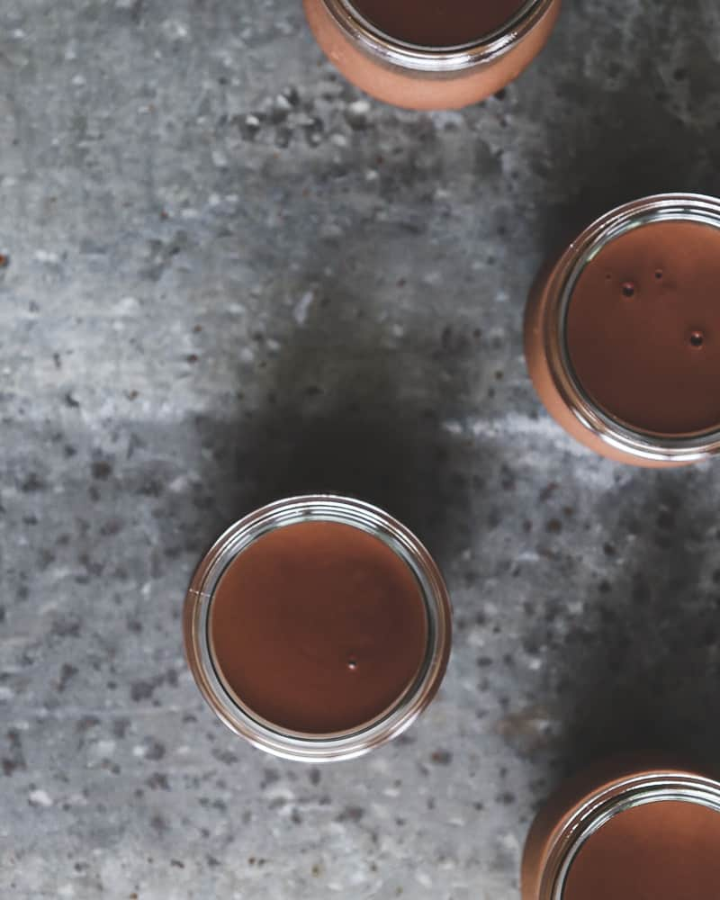 overhead photo of chocolate pots de crème in glass jars