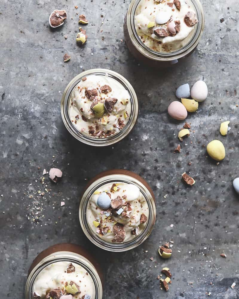 overhead photo of chocolate pots de crème topped with whipped cream and crushed candy eggs