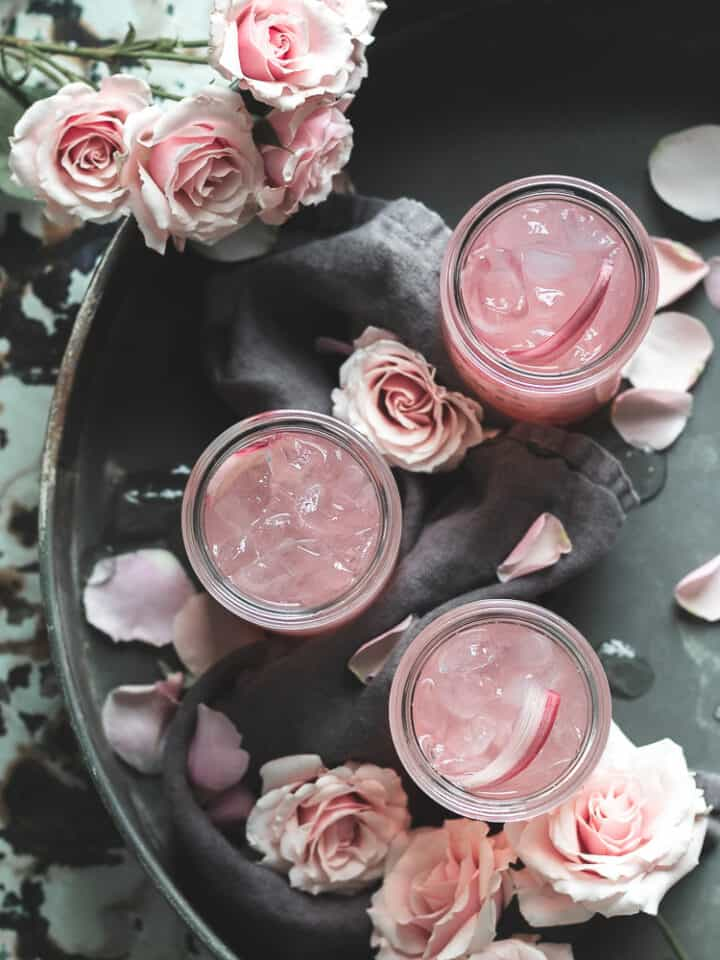overhead view of 3 rhubarb elderflower refresher cocktails in a metal tray with pink roses