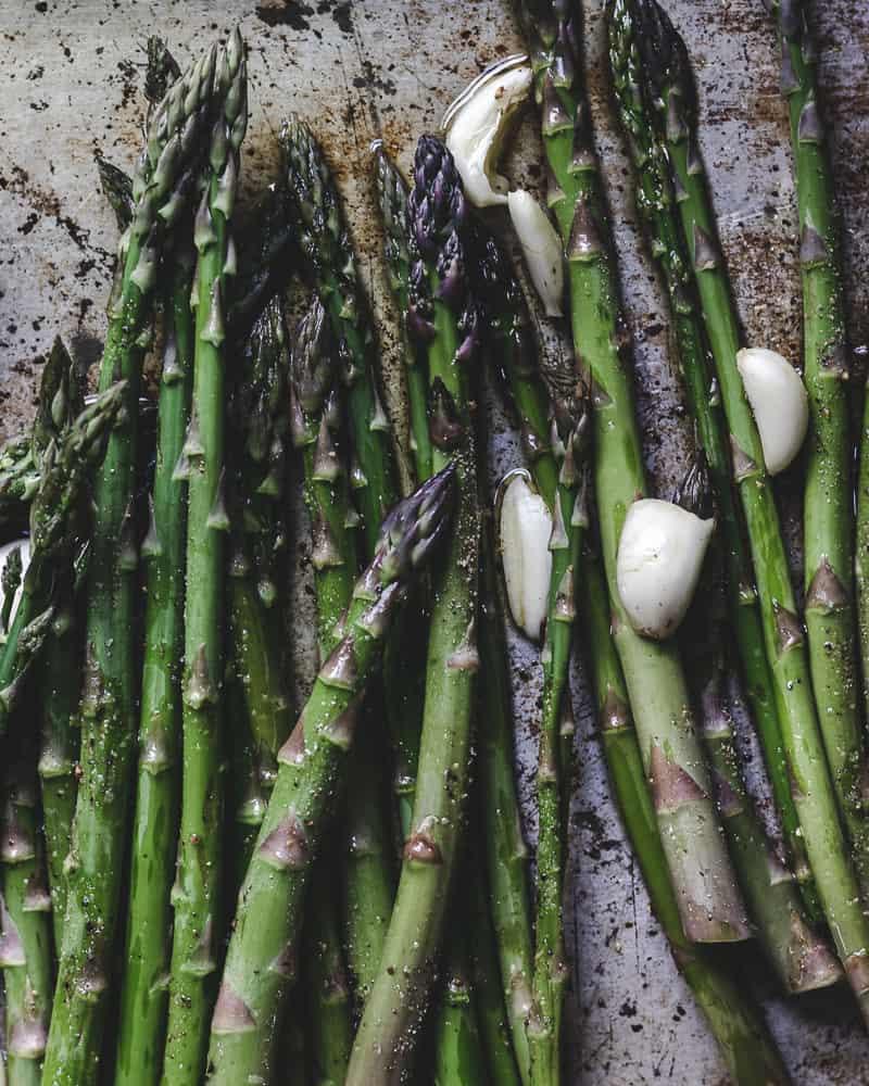 raw asparagus and garlic on metal baking tray